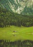 Ein sehr grünes Gebirgstal und eine kleine alpine Hütte reflektierten sich in Eibsee Stockbild
