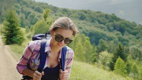 Ein sehr müder Frauentourist mit einem Rucksack geht den Gebirgsweg hinauf Willenskraft und körperliche Ausdauer stock footage