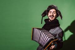 Ein sehr positiver Mann mit einem Akkordeon, das im Studio aufwirft lizenzfreies stockbild