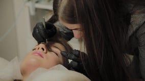 Ein sehr schönes Mädchen in einem Schönheitssalon tut eine Laminierung peitscht Kosmetiker führt die Verfahrenswimper durch stock footage