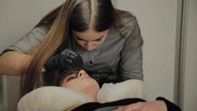 Ein sehr schönes Mädchen in einem Schönheitssalon tut eine Laminierung peitscht Kosmetiker führt die Verfahrenswimper durch stock video