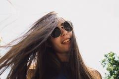 Ein sehr schönes Mädchen mit den schwarzen Gläsern, die ihr Haar wellenartig bewegen stockbilder