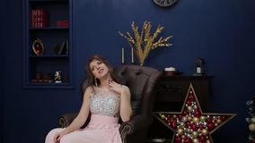 Ein sehr schönes Mädchen sitzt auf einem Lederstuhl im Dekor des neuen Jahres stock video footage