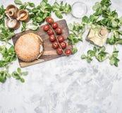 Ein selbst gemachtes Burgerhühnerkotelett und eine Beilage des Salats mit Kirschtomaten, Gewürze und Öl kochen, auf einem weißen  stockbilder