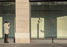 Ein Senior schaut neugierig durch ein Geschäftsfenster lizenzfreies stockbild