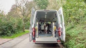 Ein Senior zog sich den Mann zurück, der hilft, Behinderter zu transportieren lizenzfreie stockbilder