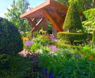 Ein Showgarten mit Blumen und Bäumen bei Chelsea Flower Show in London Lizenzfreies Stockfoto