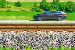 Ein sich schnell bewegendes Auto entlang der Straße geht neben den Eisenbahnlinien stockfotos