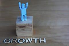 Ein Sieger mit den Armen hob nahe bei dem Wort Wachstum an Stockfoto