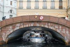 Ein Sightseeing-Tour-Boot mit Touristen geht entlang das Winter-Kanal Zimnyaya-kanavka unter die Einsiedlerei-Brücke Lizenzfreie Stockfotos
