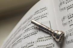 Ein silbernes Trompetenmundstück auf Notenenmusikbuch Lizenzfreie Stockfotografie