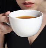 ein Sip von einer Tasse Tee Stockbild