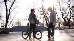 Ein Skateboardfahrer- und bmxreiter im Stadtrochenpark draußen sich treffen Freunde stehen im Rochenpark in Verbindung und herein stock video