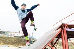 Ein Skateboardfahrerjugendlicher in einem Hut tut einen Trick mit einem Sprung auf der Rampe Ein Skateboardfahrer fliegt in die L stockfoto