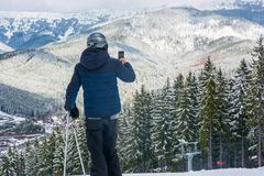 Ein Skifahrer in den Bergen fotografierte an einem Handy ein beauti Stockbild