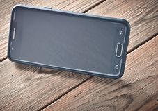 Ein Smartphone in der Position für aufpassende Filme auf einem Holztisch Lizenzfreie Stockbilder