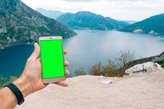 Ein Smartphone ist eine goldene Farbe mit einem grünen Schirm in den Händen Stockbild