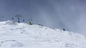 Ein Snowboarder in einem Skigebiet Skisprüngen auf einem Snowboard stock video