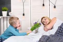 Ein Sohn mit einem Blumenstrauß von Blumen wacht seine geliebte Mutter morgens auf Das Konzept der Feier, Frauen ` s Tag Mutter`s stockfotografie
