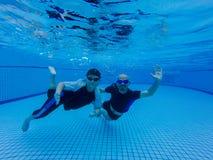 Ein Sohn und ein Vati schwimmen unter Wasser im Pool, Vati unterrichtet seinen Sohn, unter Wasser zu tauchen stockfotografie