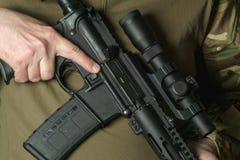 Ein Soldat, der ein Gewehr mit einem Zielfernrohr hält stockbild