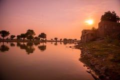 Ein Sonnenaufgang über einem See in Indien Stockbild