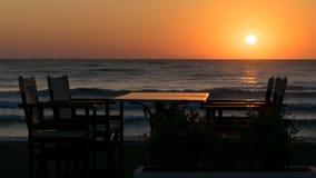 Ein Sonnenbad nehmen auf dem Strand mit Schattenbild der Sitzplätze und des Speisetisches zum Frühstück und dem Meer mit Wellen stockfoto