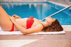 Ein Sonnenbad nehmen durch das Pool Stockfoto
