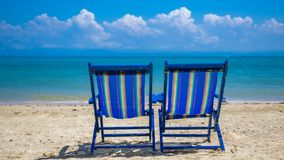 Ein Sonnenbad nehmende Betten auf Sand-Strand lizenzfreies stockfoto