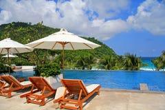 Ein Sonnenbad nehmende Betten am Swimmingpool Lizenzfreie Stockbilder