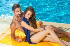 Ein Sonnenbad nehmende und trinkende Cocktails der jungen Paare Stockfotografie