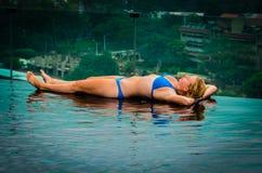 Ein Sonnenbad nehmendes Mädchen auf Rand des Unendlichkeits-Pools Lizenzfreie Stockbilder
