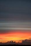Ein Sonnenuntergang über einer Ruheebene Stockfotografie