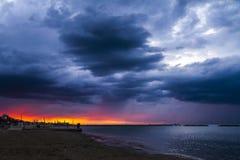 Ein Sonnenuntergang in einem Strand mit einer Raffinerie im Hintergrund Stockbilder