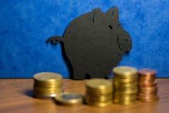 Ein Sparschwein gemacht von der schwarzen Pappe und ein Stapel Euromünzen I Stockfoto