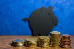 Ein Sparschwein gemacht von der schwarzen Pappe und ein Stapel Euromünzen I Lizenzfreies Stockfoto