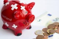 Ein Sparschwein mit die Schweiz-Flagge nahe Banknoten auf dem weißen Hintergrund Stockfotografie