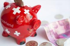Ein Sparschwein mit die Schweiz-Flagge nahe Banknoten auf dem weißen Hintergrund Lizenzfreie Stockfotos