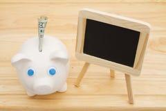 Ein Sparschwein mit Geld auf einem Schreibtisch mit Tafel lizenzfreie stockfotografie
