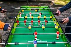 Ein Spiel des Tischfu?balls Zwei Leute, die Tischfu?ballau?enseite spielen Unterhaltung w?hrend der Feiertage oder der Freizeit J lizenzfreie stockfotos
