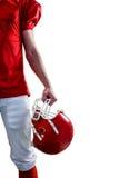 Ein Spieler des amerikanischen Fußballs, der an Hand seinen Sturzhelm nimmt Stockfotografie