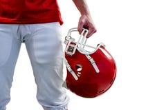 Ein Spieler des amerikanischen Fußballs, der an Hand seinen Sturzhelm nimmt stockfotos