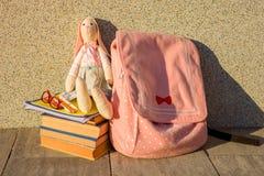 Ein Spielzeug, Gläser, Bleistifte, Notizbücher, ein Stapel von Büchern und ein Rucksack Lizenzfreies Stockbild