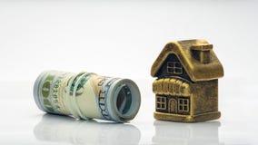 Ein Spielzeuggoldhaus steht nahe bei einer Rolle von US hundert Dollarscheine Konzepthypothek, Darlehen, Bürgschaft, Finanzinvest stockfotos