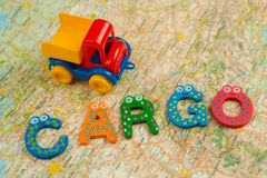 Ein Spielzeuglastwagen transportiert eine Fracht auf einer Tabelle mit einer Karte und einem Notizblock Stockfoto