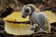 Ein Spielzeugpferd in den Blättern und im Gras Lizenzfreies Stockfoto