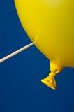 Ein spitzes stickand ein gelber Ballon auf b Stockbild