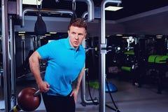 Ein sportlicher blonder Mann, der Übungen mit Ball in der Turnhalle tut Lizenzfreie Stockbilder