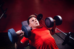 Ein sportlicher blonder Mann, der Übungen mit Dummköpfen in der Turnhalle tut Lizenzfreie Stockfotos
