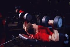 Ein sportlicher blonder Mann, der Übungen mit Dummköpfen in der Turnhalle tut Stockfoto
